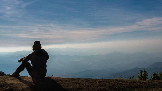 silhouette-d-39-un-homme-qui-assis-et-regardant-par-dessus-le-fond-de-paysage-de-montagnes_41418-1968.jpg